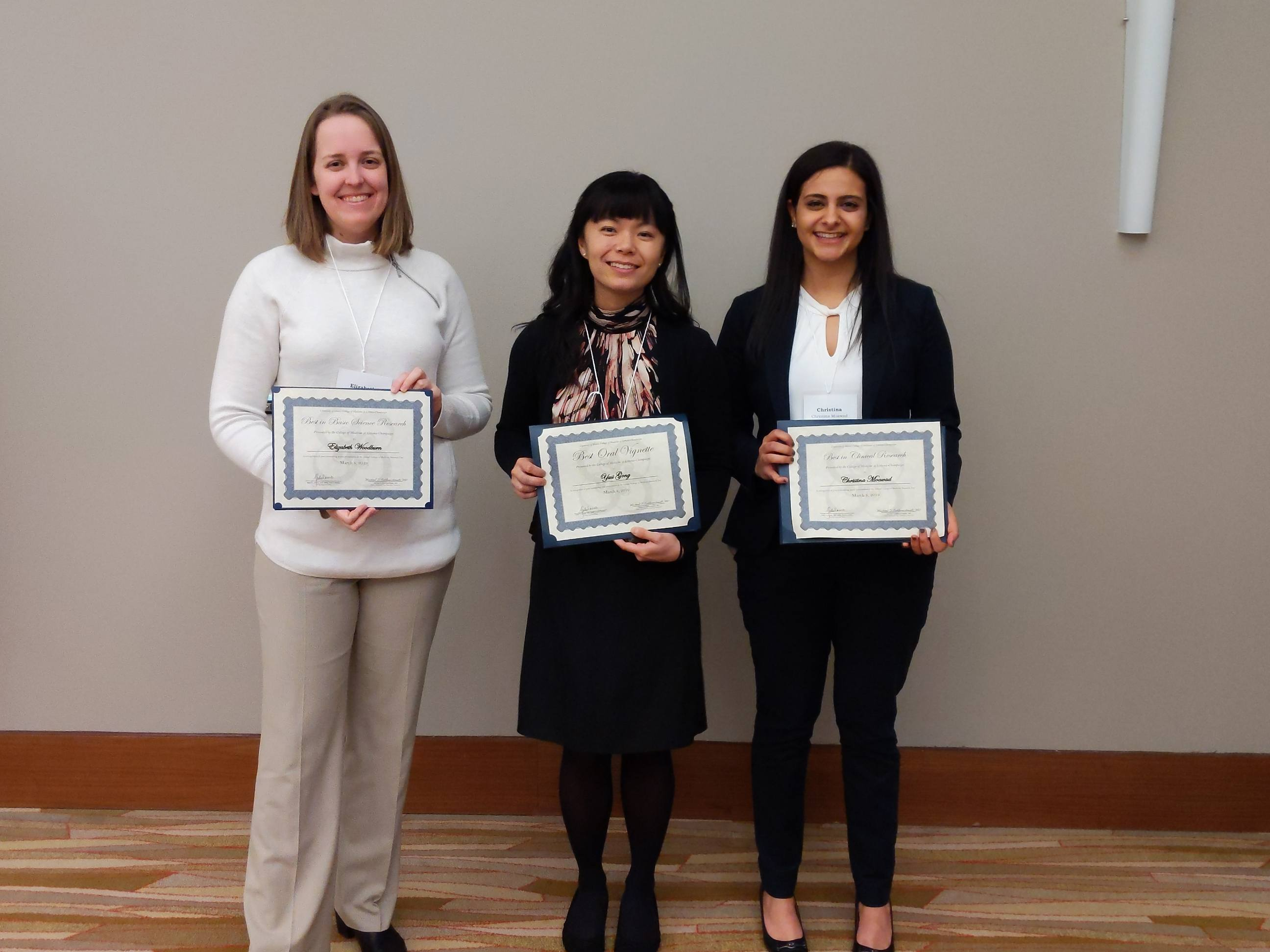 Carle Illinois students, Elizabeth Woodburn, Yusi Gong, and Christina Moawad, receiving their awards at the University of Illinois College of Medicine at Urbana-Champaign Research Day.