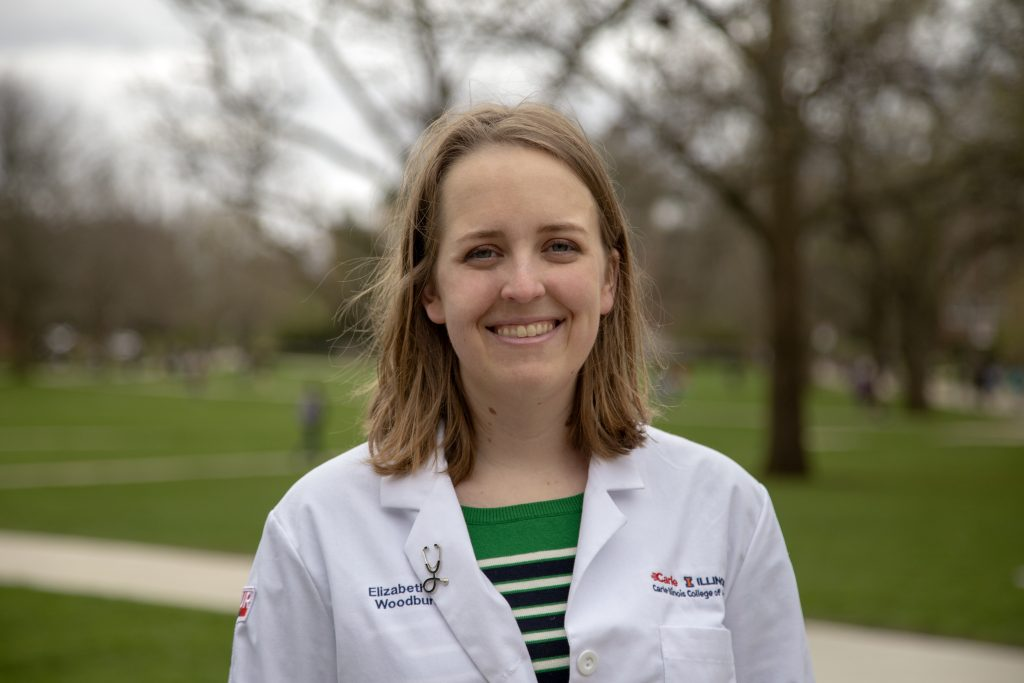 Elizabeth Woodburn, Carle Illinois medical student, in her white coat on the University of Illinois quad.
