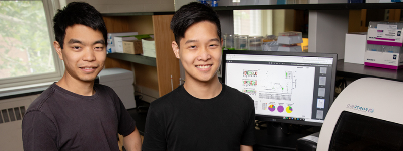 Professor Wu and graduate student posing in front of research